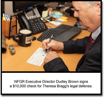 NFGR Executive Director Dudley Brown signs a check for Theresa Bragg's legal defense.